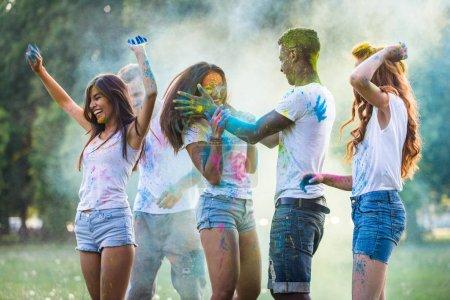 Photo pour Groupe d'amis heureux jouant avec les couleurs holi dans un parc - Jeunes adultes s'amusant lors d'un festival holi, concepts sur le plaisir, amusant et jeune génération - image libre de droit