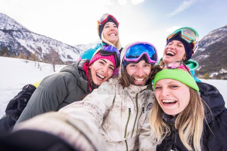 Photo for Happy group of people having fun on winter vacation - Friends witn snow suit partying outdoors - Royalty Free Image