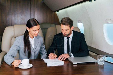 Photo pour Homme d'affaires et femme travaillant lors d'un voyage sur jet privé - Portrait de prendre un vol de première classe pour le travail, concepts de business et de la mobilité des gens d'affaires - image libre de droit