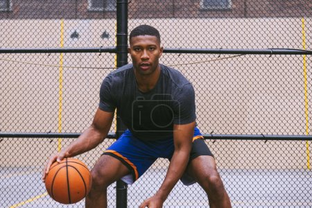 Photo for Basketball player training on a court in New york city - Royalty Free Image