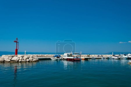 Port of Tucepi in Croatia with ships and lighthous...