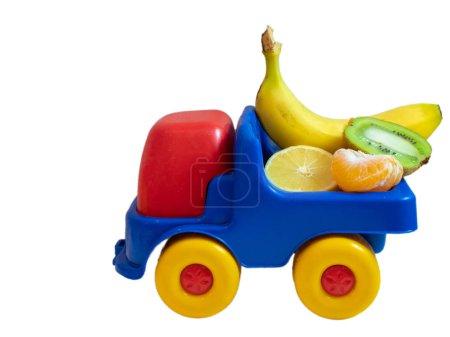 banana, kiwi, mandarine, lemon - exotic fruits on toy car truck. ogranic food delivery service concept. side shot isolated on white background