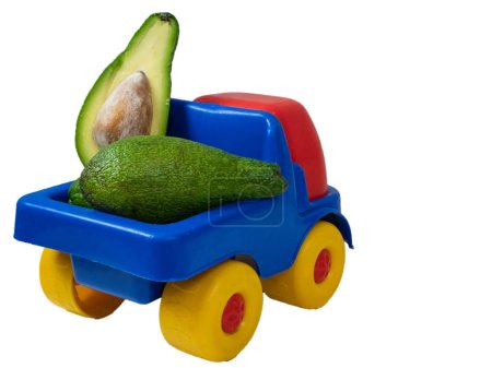 big toy truck with avocado fruit cut in a half. closeup from behind back shot isolated on white background