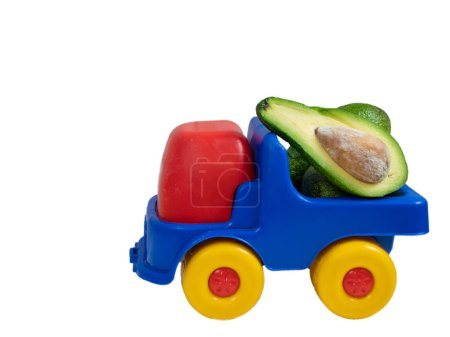 big toy truck with avocado fruit cut in a half. closeup side shot isolated on white background