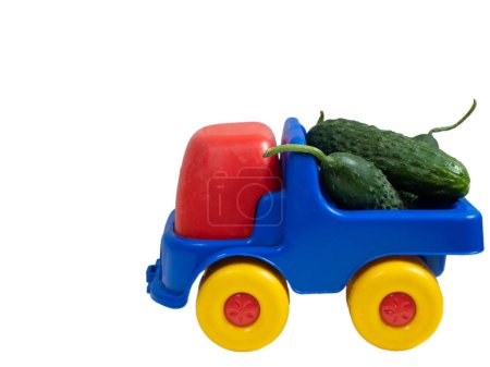 colorful vivid toy car truck with fresh green cucumbers. closeup side shot cutout isolated on white background
