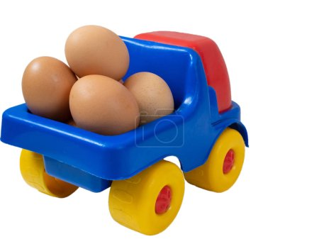 little toy truck full of fresh organic farm yellow eggs. vegetarian farm food market delivery service concept. back closeup shot cutout isolated on white background