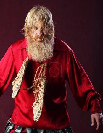 Photo pour Portrait d'un homme vêtu d'une chemise rouge à la barbe aux cheveux longs et moustache avec un bâton et des chaussures bast en atelier mains sur fond bordeaux - image libre de droit