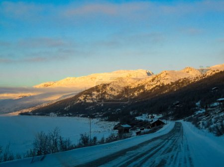 Photo for Driving at golden sunrise through mountains and village in Norway. Sunshine on a mountain top. - Royalty Free Image