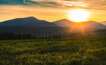 Povazsky Inovec Hill in Slovakia with small village in the valley on sunset. Landscape photo of wheat field with green grass and beautiful sun rays. Perfect view point from meadow on sunset.