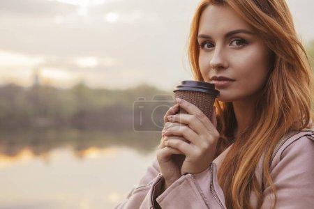 """Photo pour Cheveux rouges sexy plus taille femme marchant sur un parc. Par temps froid, elle porte une veste en cuir. Elle boit du café de la tasse """"to go"""". Superbe coucher de soleil sur un fond. Espace de copie - image libre de droit"""