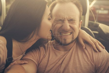 Photo for Gorgeous sexy copule of man and woman on a vacation car trip in summer day. Luxury grey sport car. Sexy fit brunette woman and man in casual outfit. Sunset. - Royalty Free Image