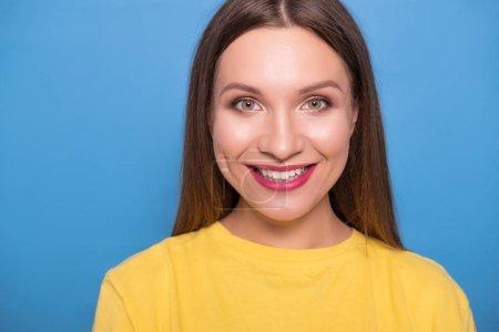 Photo pour Jolie femme brune aux cheveux longs posant en t-shirt jaune sur fond bleu. Portrait émotionnel. Elle sourit joyeusement avec des dents blanches impeccables - image libre de droit