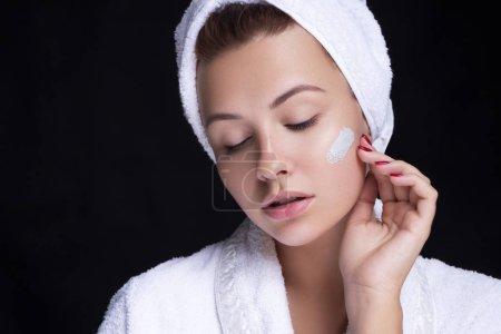 Photo pour Belle jeune femme européenne applique un masque d'argile sur son visage. concept de spa beauté . - image libre de droit