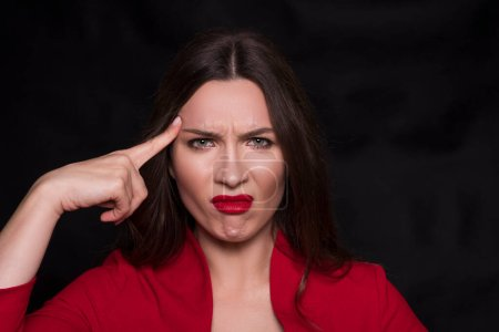 Photo for Emotional head shot portrait of a brunette caucasian woman in red dress and with red lips on black background. She make unhappy, dusgusting emotions. - Royalty Free Image