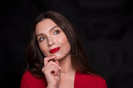 Photo for Emotional head shot portrait of a brunette caucasian woman in red dress and with red lips on black background. She thoughtful. - Royalty Free Image