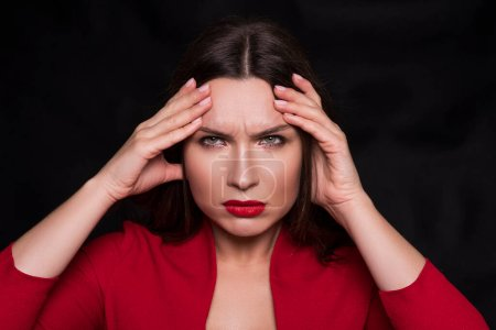 Photo for Emotional head shot portrait of a brunette caucasian woman in red dress and with red lips on black background. She have a headache, with fingers on her head. - Royalty Free Image