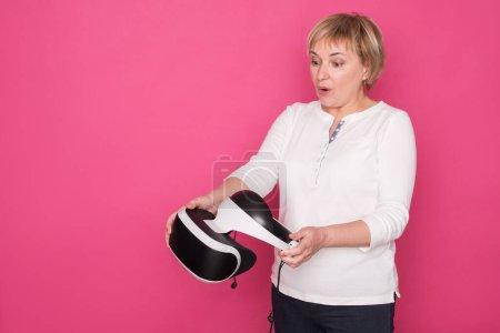 Photo pour Les personnes âgées dans les années 60 femme joue dans le casque VR. Elle se tient en chemisier blanc sur fond rose et semble heureuse. - image libre de droit