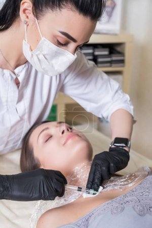 Photo pour Médecin cosmétologue faire une procédure d'injection à une femme dans sa clinique. Elle porte des lueurs noires et un masque et tient la seringue avec une aiguille. - image libre de droit
