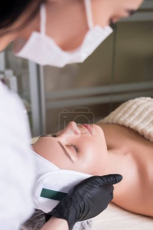 Photo for Cosmetologist doctor apply alcaline wash peeling on client face in her cabinet in clinic - Royalty Free Image