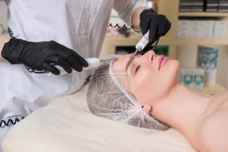 Photo for Cosmetologist doctor make ultrasound peeling to a woman client in her clinic. - Royalty Free Image
