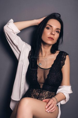 Photo for Brunette slim woman in sexy outfit on a neutral background. Studio portrait in seductive poses. - Royalty Free Image