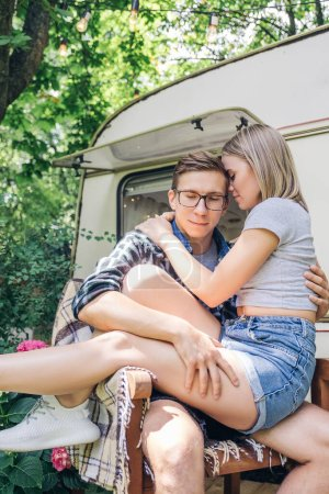 Photo for Cute young couple in love near cabin house. They hugging and kissing and are sweet and caring to each other. Summer daylight portrait in casual outfit, outdoors. Copy space. - Royalty Free Image