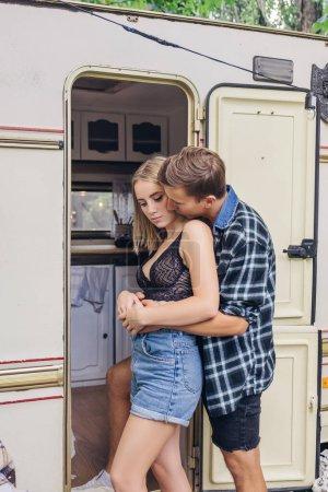 Photo pour Joli jeune couple amoureux près de la cabane. Ils s'embrassent et s'embrassent et sont doux et attentionnés les uns envers les autres. Portrait d'été en tenue décontractée, à l'extérieur. Espace de copie. - image libre de droit