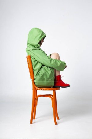 young pretty woman wearing green oilskin with hood and red boots  sitting on chair