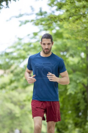 young sporty man jogging in summer park