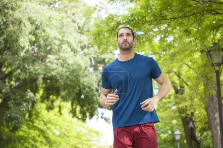 attractive fit young man running in the park, healthy lifestyle