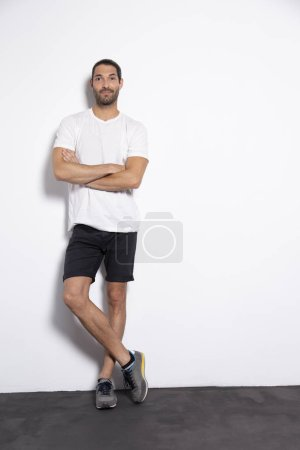 Attractive caucassian young man with brown hair on white background with natural shadow.  Studio sport session