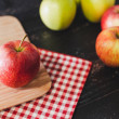 Group of apples on wooden cutting board with napki...