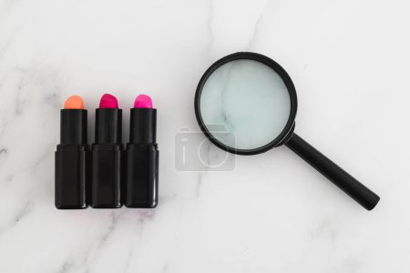 Photo pour Analyzing make-up ingredients concept, set of lipsticks with magnifying glass - image libre de droit