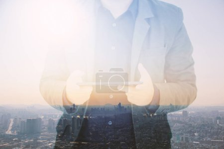 Businessman using digital tablet,double exposure of businessman blur background.