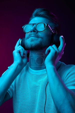 Photo for Handsome man in glasses enjoys listening to music with headphones. Neon studio portrait - Royalty Free Image