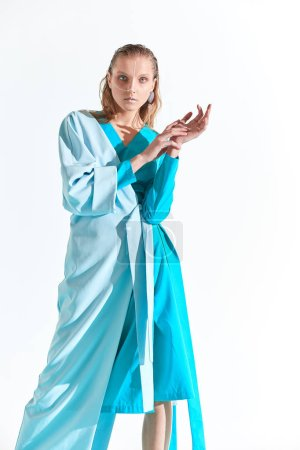 Photo for Fashion portrait of young blonde woman with blue eyes and painted white lines on face, dressed in turquoise dress. White background - Royalty Free Image