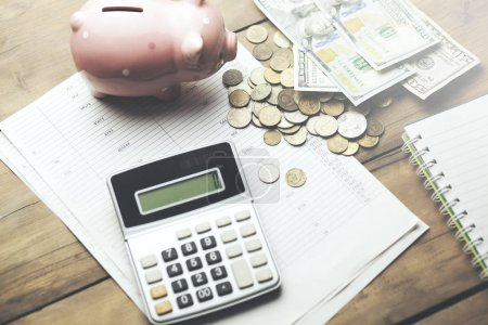 piggy bank with cash and calculator on business documents background