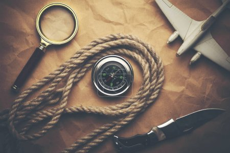 aircraft, compass and rope on crumpled paper
