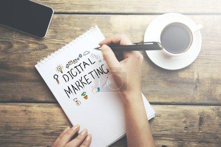 woman written digital marketing text on notepad on desktop