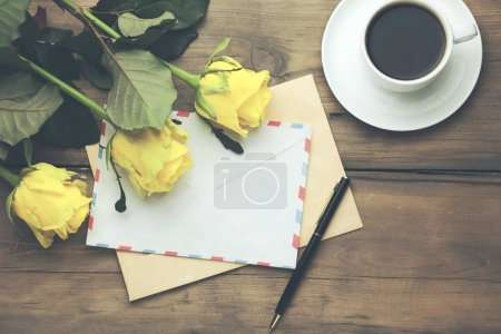 yellow roses with page and coffee on the wooden table