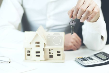 male hands holding key over table with house model