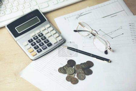 Photo pour Calculatrice avec des documents, pièces de monnaie et clavier en table de bureau - image libre de droit