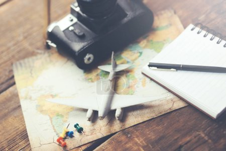 Photo for Travel accessories: camera, map, airplane with notepad  on wood background - Royalty Free Image