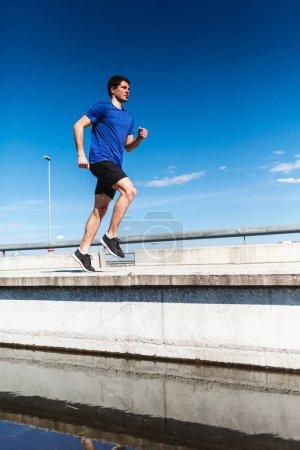Handsome man in blue t-shirt jogging on bridge against blue sky background