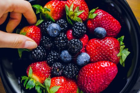 Female hand taking strawberry from plate full of berries