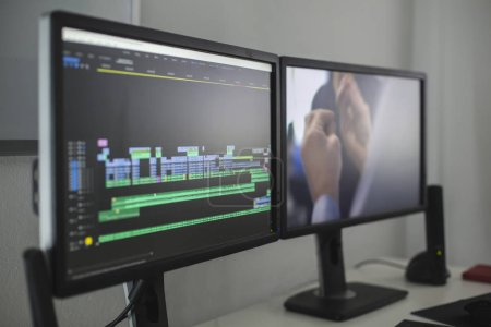 Cropped view of computer monitors with video editor on desk