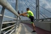 Male runner stretching legs on railing of bridge