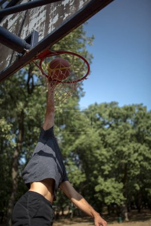 Male athletic basketball player trowing ball in net