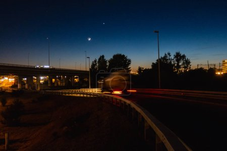 Overpass at night with moon in the background