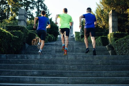 Photo for Three professional male athletes running up staircase in park - Royalty Free Image